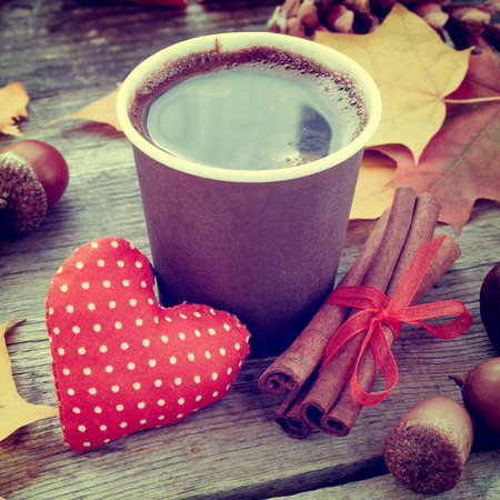 coffee cup, red heart and autumn still life on old table photo