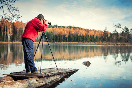 old photograph: man photographer with camera on a pier, autumn landscape
