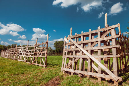 grass verge: wooden rustic fence, blue sky and village landscape Stock Photo