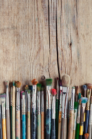 messy paint: row of artist paintbrushes on old wooden rustic table