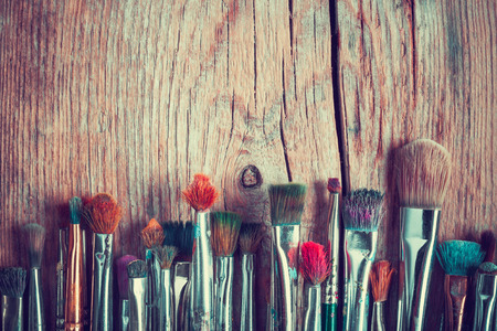 row of artist paintbrushes closeup on old wooden rustic table, retro stylized Stockfoto