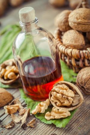 aceite de cocina: Nueces, botella de tintura o aceite y cesta de mimbre con nueces en mesa de la cocina antigua.