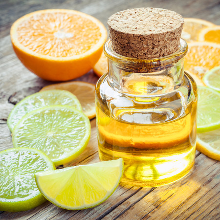 Citrus essential oil and slice of ripe fruits: orange, lemon and lime fruits