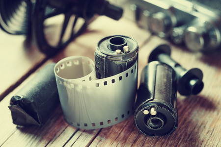 photo: Old photo film rolls, cassette and retro camera. Vintage stylized.