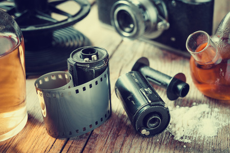 reagents: Old photo film rolls, cassette, retro camera and chemical reagents for photographic film. Vintage stylized. Stock Photo