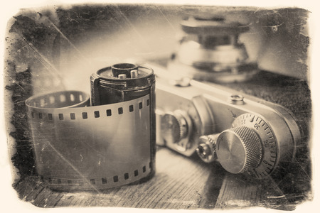 developing: Old photo film roll and retro camera on desk. Vintage stylized photo. Stock Photo