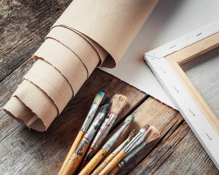 priming brush: Artist canvas in roll, canvas stretcher and paintbrushes on old table Stock Photo