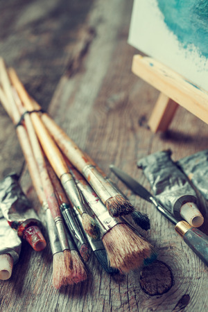 Artistic paintbrushes, tubes of oil paint, palette knife and easel with oil painting on old wooden desk.