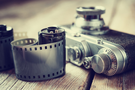 photography: Old photo film rolls, cassette and retro camera, selective focus. Vintage stylized.