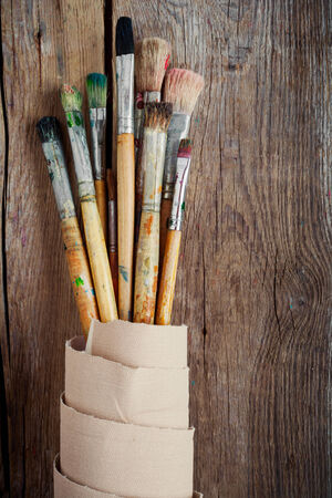Artist paintbrushes and roll of canvas on wooden background photo