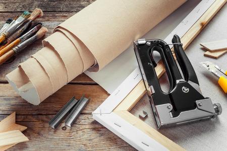 paleta: Lienzo Artista en rollo, camilla de lona, ??pistola de grapas y pinceles en la mesa de edad Foto de archivo