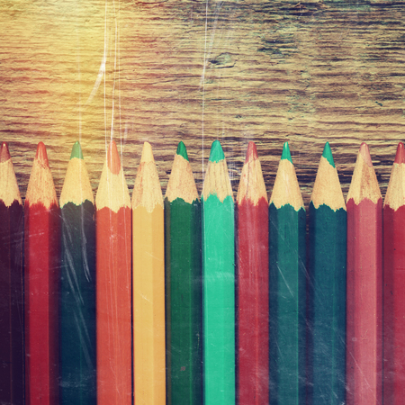 Row of colored drawing pencils closeup on old desk. Vintage stylized image. photo