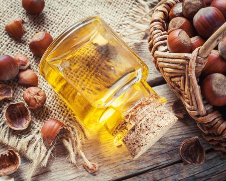aceite de cocina: Botella de aceite de nuez y cesta con avellanas en la mesa de la cocina antigua. Vista superior.