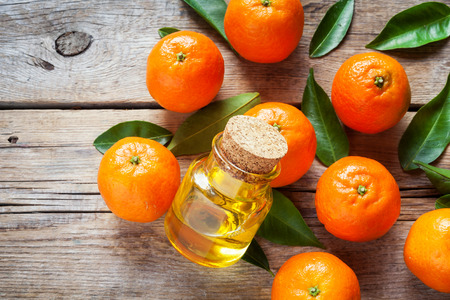 Ripe tangerines with leaves and bottle of essential citrus oil on a wooden table.