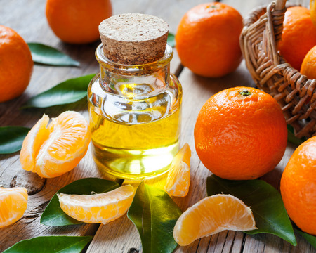 Bottle of essential citrus oil and ripe tangerines with leaves on old wooden kitchen table.
