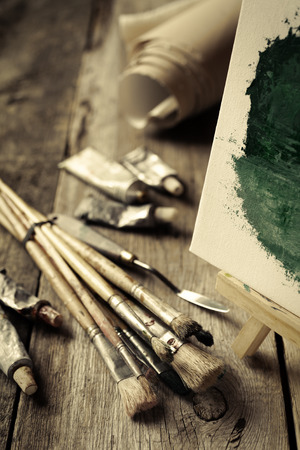 artist: Artistic paintbrushes, tubes of oil paint, palette knife and easel with oil painting on old wooden desk. Vintage stylized photo. Stock Photo