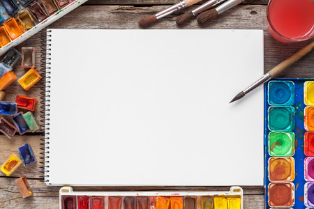 Set of watercolor paints,  brushes for painting and blank white paper sheet of sketchbook on vintage wooden background. Top view.