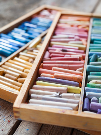 paint box: Set of multicolored professional artistic pastel crayons in open wooden box on table. Selective focus.