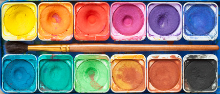 paint box: Set of watercolor paints and paintbrush. Top view. Stock Photo