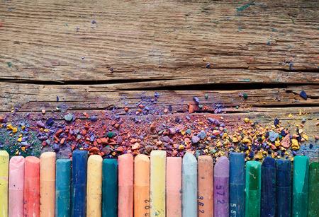 Pastellkreiden und Pigmentstaub auf alte hölzerne Hintergrund. Lizenzfreie Bilder