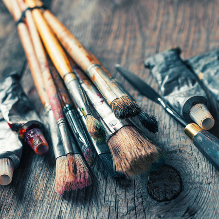 Artistic paintbrushes, tubes of oil paint, palette knife on old wooden desk. Vintage stylized.