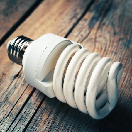 Close up of energy saving light bulb on wooden background. Vintage stylized. photo
