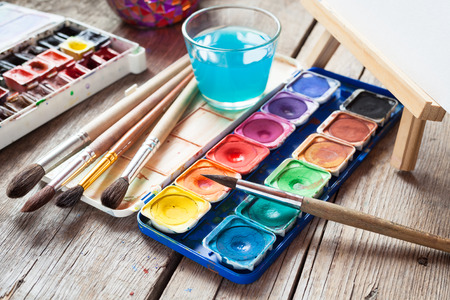 paint box: Box of watercolor paints, art brushes, glass of water and easel with canvas or paper on old wooden table.
