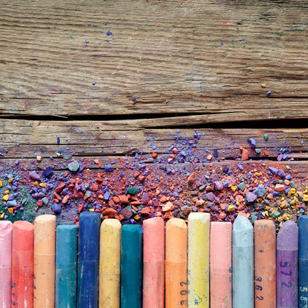 vibrant color: Artistic pastel crayons and pigment dust on old rustic wooden background. Stock Photo