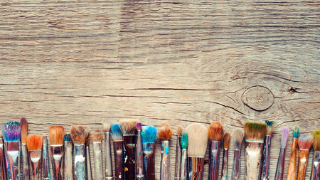 Row of artist paintbrushes closeup on old wooden rustic background Archivio Fotografico