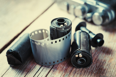photographic: Old photo film rolls, cassette and retro camera on background. Vintage stylized.