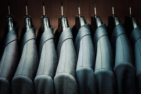 Rij van mannen colberts op hangers Stockfoto