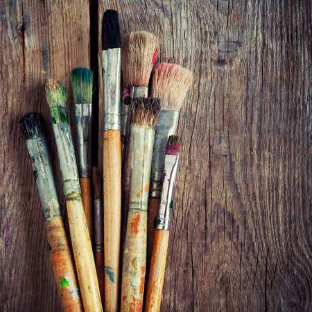 art palette: Bunch of old artist paintbrushes on wooden rustic table