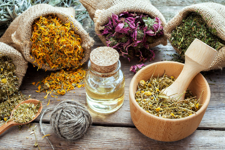 essential oil: Healing herbs in hessian bags, mortar with chamomile and essential oil on wooden table, herbal medicine.