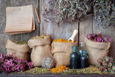 medicamentos: Hierbas curativas en bolsas de arpillera cerca de la pared de madera Foto de archivo