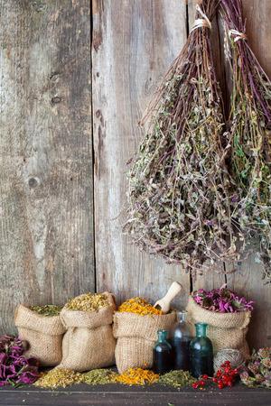 herbs: Hierbas curativas en bolsas de arpillera cerca de la pared de madera r�stica Foto de archivo