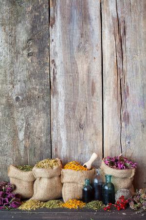 huile: Herbes m�dicinales dans des sacs de jute sur fond vieux bois