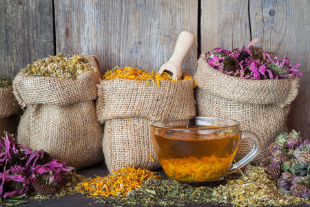 Healing herbs in hessian bags and healthy tea cup photo