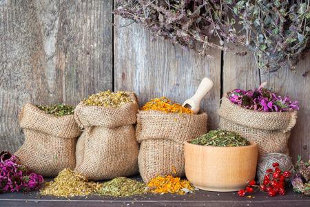 Gedroogde geneeskrachtige kruiden in jute zakken en in mortel op houten muur achtergrond, kruidengeneeskunde. Stockfoto