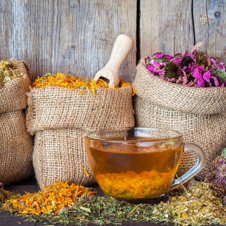 Heilende Kräuter im hessischen Taschen und gesunden Tee-Tasse auf rustikalem Holzuntergrund, Kräutermedizin.