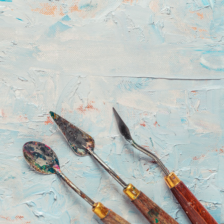 priming paint: three old palette knifes on artist canvas with coating of oil paint Stock Photo