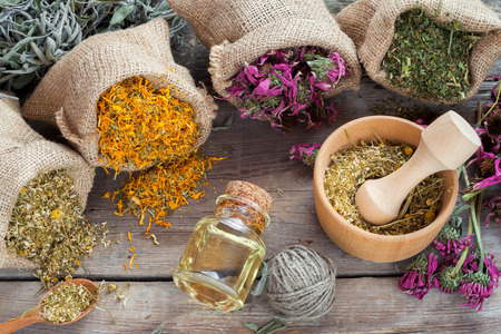 Healing herbs in hessian bags, wooden mortar with chamomile and essential oil on rustic table, herbal medicine. Archivio Fotografico