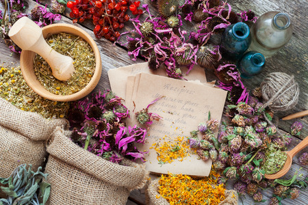 Healing herbs in hessian bags, wooden mortar, bottles with tincture, herbal medicine. Top view.