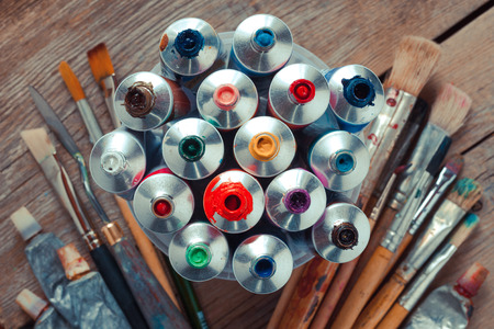 Vintage stylized photo of oil multicolor paint tubes closeup and artist paintbrushes on wooden desk. Top view.