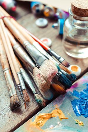 paintbrushes: Vintage stylized photo of paintbrushes closeup, artist palette and multicolor paint tubes.