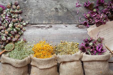 Healing herbs in hessian bags on old wooden rustic table, herbal medicine. Top view.