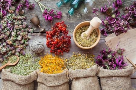 mortero: Hierbas curativas en bolsas de arpillera, mortero de madera, pequeñas botellas en tabla de madera, hierbas medicinales. Vista superior.