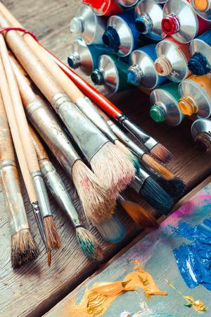 Jahrgang stilisierte Foto von Pinseln closeup, offene multicolor Farbtuben und Künstlerpalette. Standard-Bild