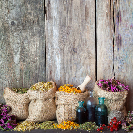 Healing herbs in hessian bags and blue bottles with tincture on old wooden background, herbal medicine.