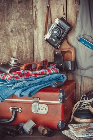 古い旅行のスーツケース、スニーカー、服、サングラス、マップ、写真、レトロなフィルム カメラ。様式化されたヴィンテージ。