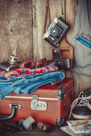 Old travel suitcase, sneakers, clothing, sunglasses, maps, filmstrip and retro film camera . Vintage stylized. Banque d'images